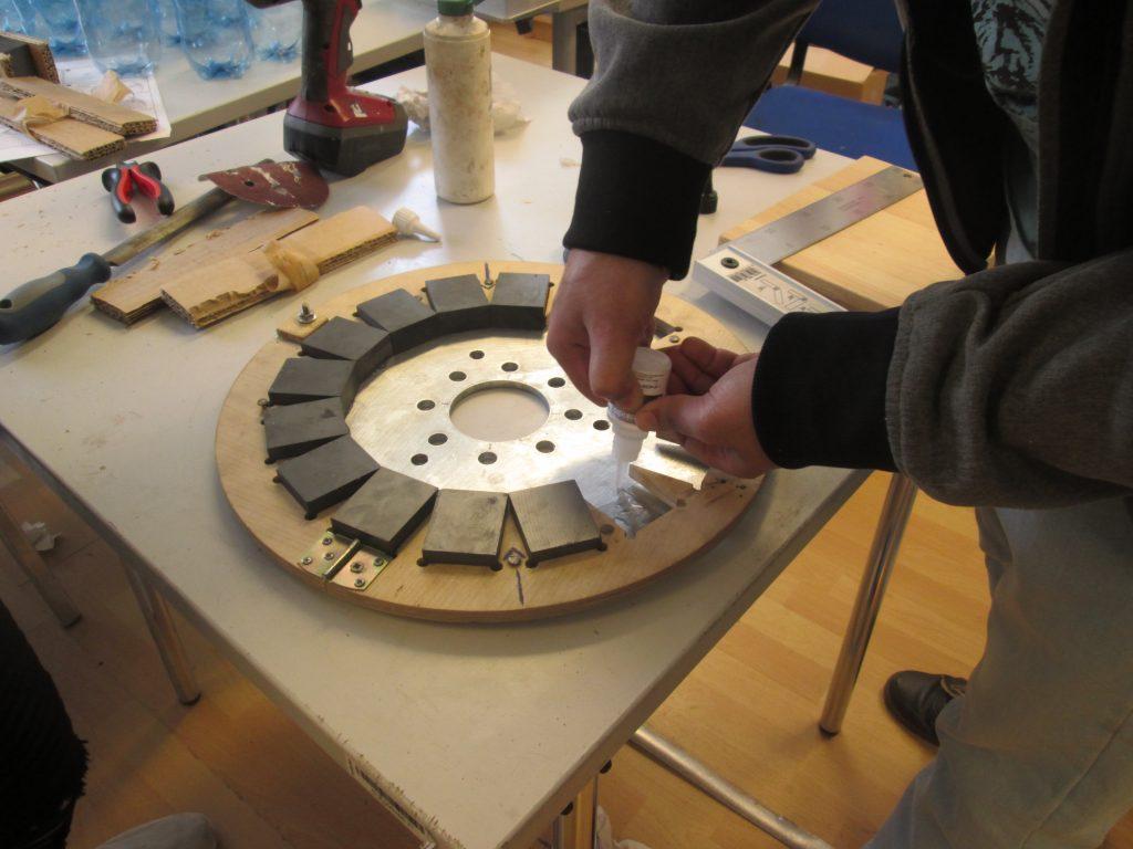 Windrad JBZ Wr. Neustadt: Teilnehmer klebt Magnete mithilfe einer Schablone